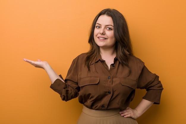 Jonge bochtige russische vrouw die een exemplaar op een palm toont en een andere hand op taille houdt.
