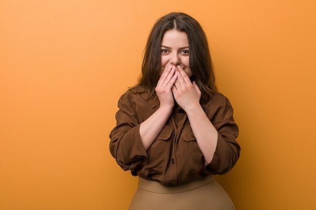Jonge bochtige russische vrouw die om iets lacht, die mond behandelt met handen.