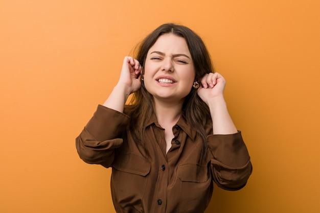 Jonge bochtige russische vrouw die oren behandelt met zijn handen