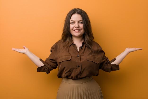Jonge bochtige russische vrouw maakt schaal met armen, voelt zich gelukkig en zelfverzekerd.