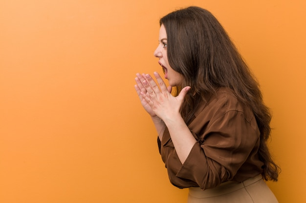 Jonge bochtige russische vrouw schreeuwt luid, houdt ogen open en handen gespannen.