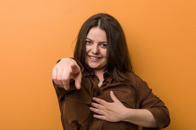 Jonge bochtige russische vrouw wijst met duimvinger weg, lachend en zorgeloos.