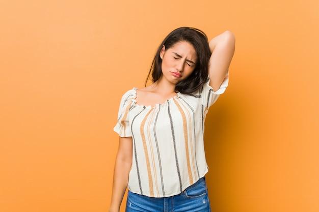 Jonge bochtige vrouw die aan nekpijn lijdt vanwege een zittende levensstijl