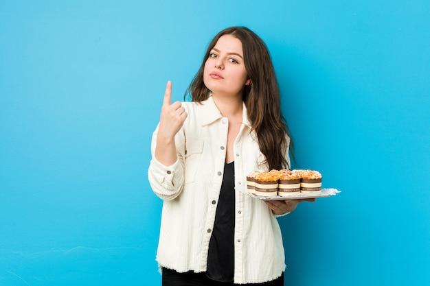 Jonge bochtige vrouw die een cupcakes houdt die met de vinger naar je wijst alsof het uitnodigen dichterbij komt.