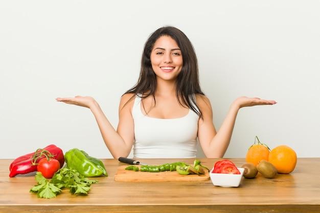 Jonge bochtige vrouw die een gezonde maaltijd bereidt, maakt schaal met armen, voelt zich gelukkig en zelfverzekerd.