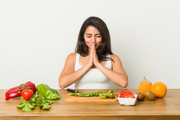 Jonge bochtige vrouw die een gezonde maaltijd hand in hand voorbereidt bidden dichtbij mond, voelt zelfverzekerd.