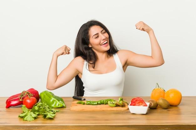 Jonge bochtige vrouw die een gezonde maaltijd voorbereidt die vuist opheft na een overwinning, winnaarconcept.