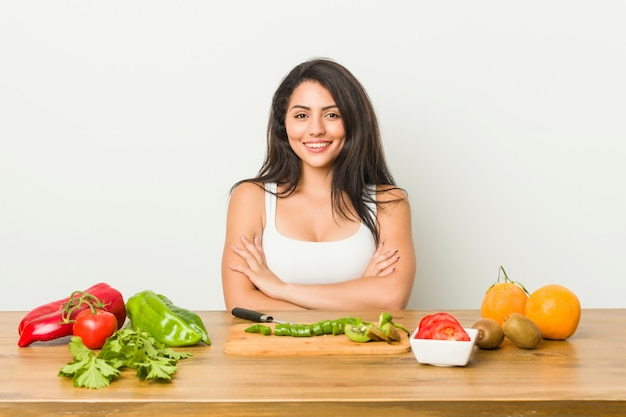 Jonge bochtige vrouw die een gezonde maaltijd voorbereidt die zich zeker voelt, gekruiste armen met vastberadenheid.