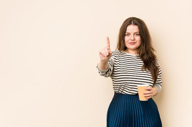Jonge bochtige vrouw die een koffie houdt die nummer één met vinger toont