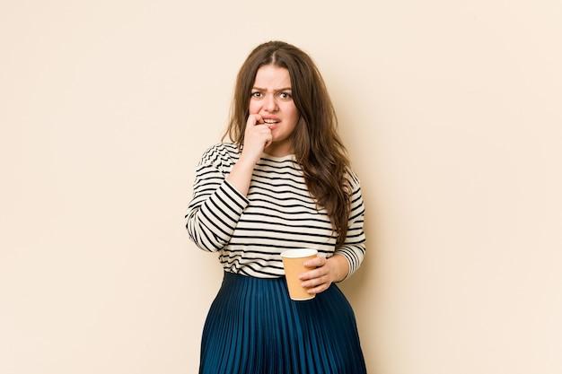Jonge bochtige vrouw die een koffie houdt die vingernagels bijt, zenuwachtig en zeer bezorgd.