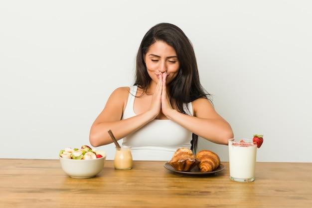 Jonge bochtige vrouw die een ontbijt neemt, hand in hand bidt in de buurt van de mond, voelt zich zelfverzekerd.