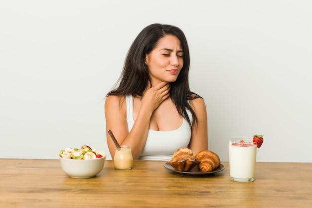Jonge bochtige vrouw die een ontbijt neemt, lijdt pijn in de keel door een virus of infectie.