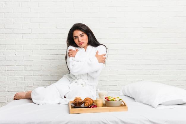 Jonge bochtige vrouw die een ontbijt neemt op het bed dat koud gaat vanwege lage temperatuur of een ziekte.
