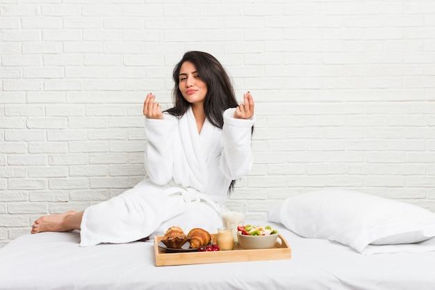 Jonge bochtige vrouw die een ontbijt op het bed neemt dat aantoont dat zij geen geld heeft.