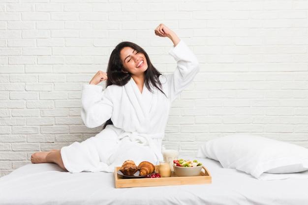 Jonge bochtige vrouw die een ontbijt op het bed neemt dat vuist opheft na een overwinning, winnaarconcept.