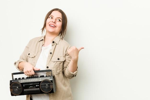Jonge bochtige vrouw die een retro radio houdt wijst met duimvinger weg, lachend en zorgeloos.