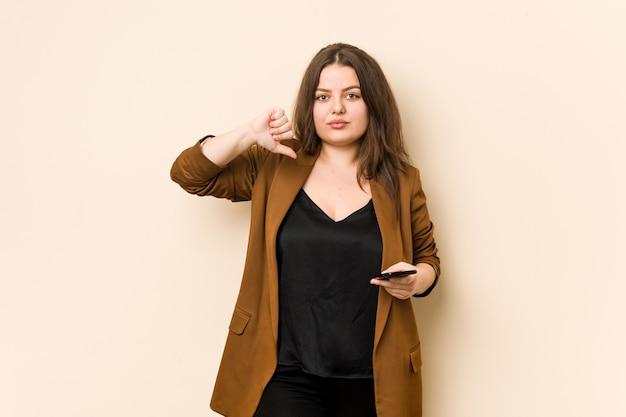 Jonge bochtige vrouw die een telefoon houdt die een afkeergebaar toont, duimen naar beneden. meningsverschil concept.
