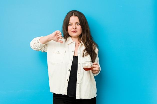 Jonge bochtige vrouw die een theekop houdt die een afkeergebaar toont, duimen naar beneden. meningsverschil concept.