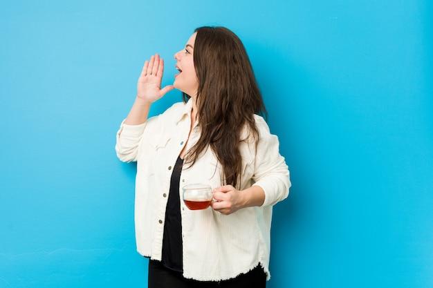 Jonge bochtige vrouw die een theekop houdt die en palm dichtbij geopende mond houdt.