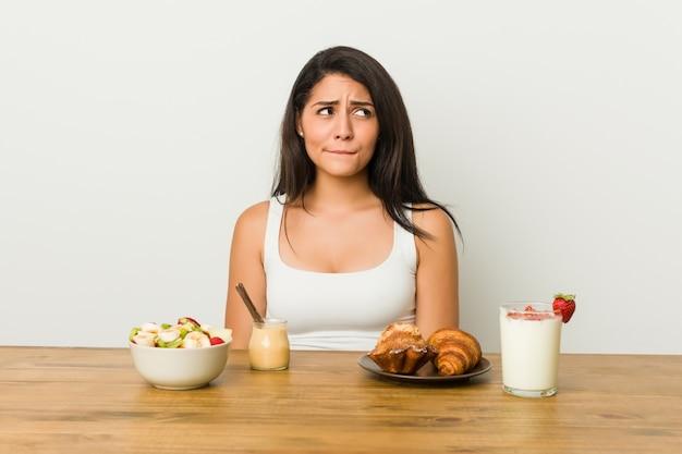 Jonge bochtige vrouw die een verward ontbijt neemt, voelt zich twijfelachtig en onzeker.