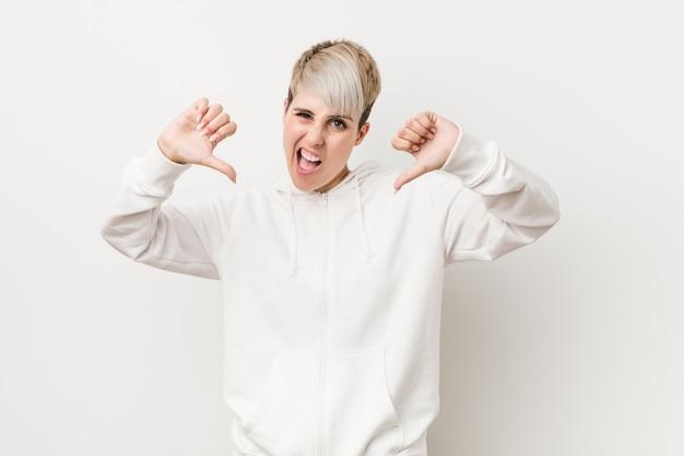 Jonge bochtige vrouw die een witte hoodie draagt die duim toont en afkeer uitdrukt.