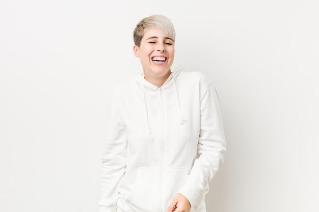 Jonge bochtige vrouw die een witte hoodie draagt, lacht en sluit de ogen, voelt zich ontspannen en gelukkig.