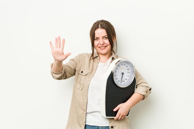 Jonge bochtige vrouw die schaal glimlachend vrolijk tonend nummer vijf met vingers houdt.