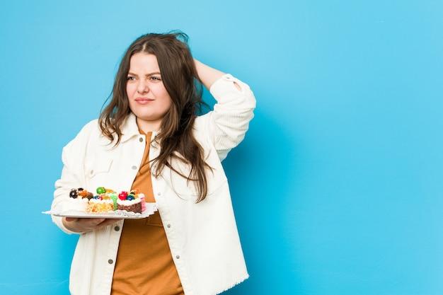 Jonge bochtige vrouw die zoete cakes houden wat betreft achterhoofd, denkend en het maken van een keus.