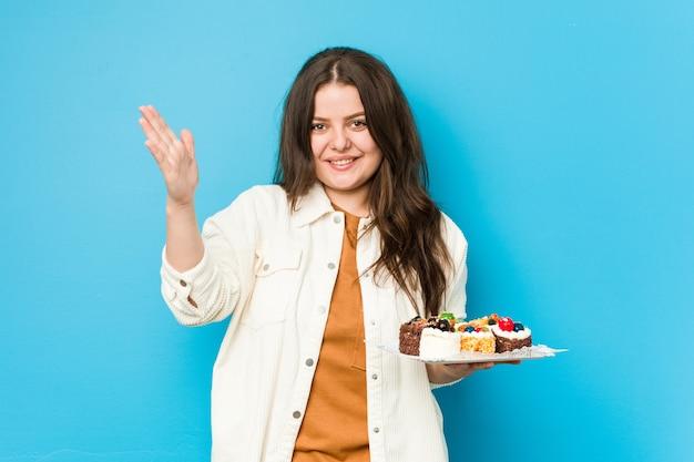 Jonge bochtige vrouw die zoete cakes houdt die een aangename verrassing ontvangen, opgewonden en handen opheffen.
