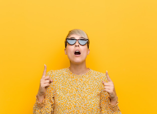 Jonge bochtige vrouw draagt een floral zomer kleding wijzende bovenkant met geopende mond.