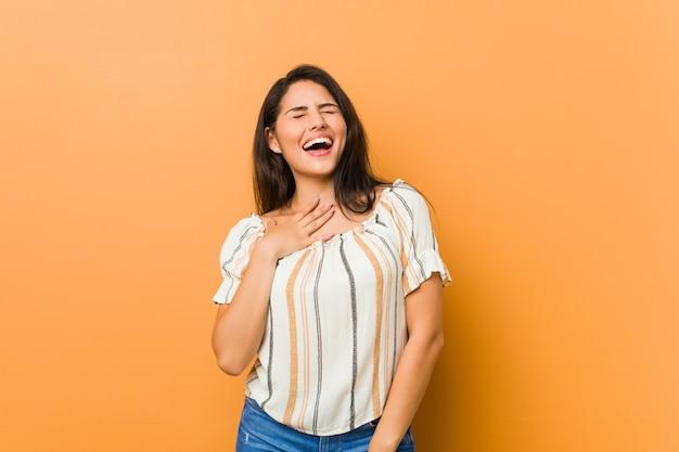 Jonge bochtige vrouw lacht hardop terwijl ze de hand op de borst houdt.