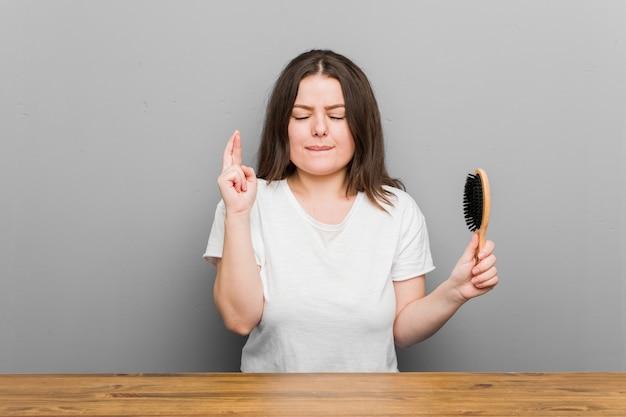Jonge bochtige vrouw met een grote maat die een haarborstel houdt die de vingers kruist om geluk te hebben