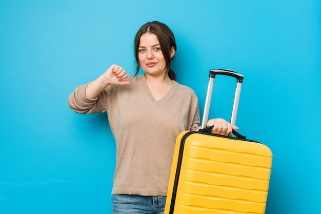 Jonge bochtige vrouw met een koffer voelt zich trots en zelfverzekerd, een voorbeeld om te volgen.