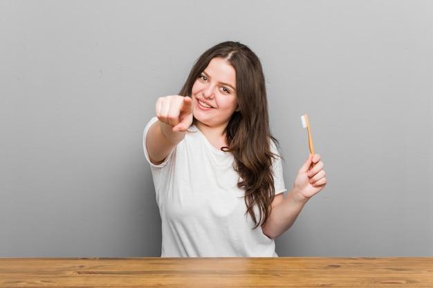 Jonge bochtige vrouw met een tandenborstel vrolijke glimlach wijzend naar de voorkant