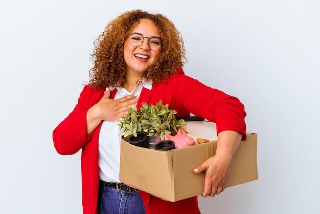 Jonge bochtige vrouw verhuizen naar een nieuw huis geïsoleerd op een witte achtergrond lacht hardop hand op de borst te houden.
