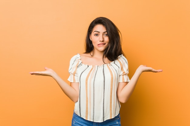 Jonge bochtige vrouw verward en twijfelachtig schouders ophalen om een kopie ruimte te houden.