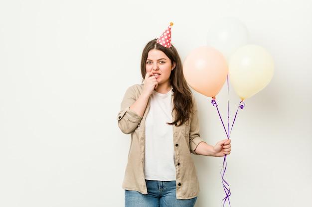 Jonge bochtige vrouw viert een verjaardag bijtende nagels, nerveus en erg angstig