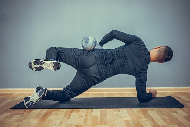 Jonge bodybuilder die oefening met kettlebell doet. achteraanzicht van gespierde man met perfecte lichaamsbouw op grijze achtergrond. kracht en motivatie.