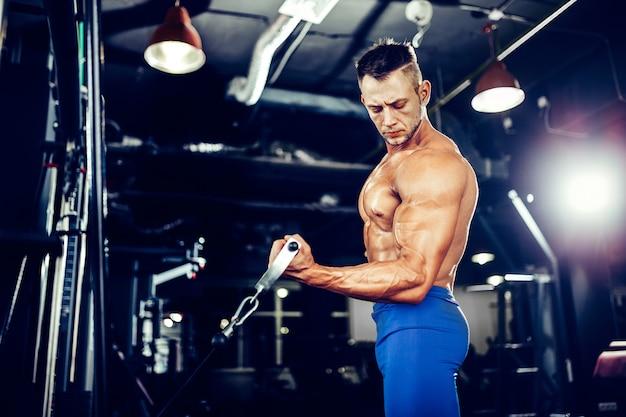 Jonge bodybuilder die oefening voor bicepsen doet