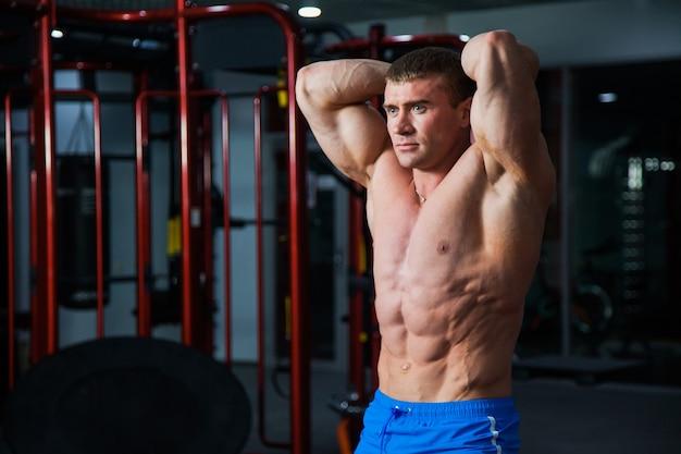 Jonge bodybuilder tonen sterk gespierd lichaam op sportschool. fit man vormt bij sportclub