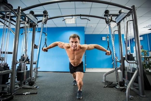 Jonge bodybuilder werkt aan zijn borst met kabel crossover in de sportschool