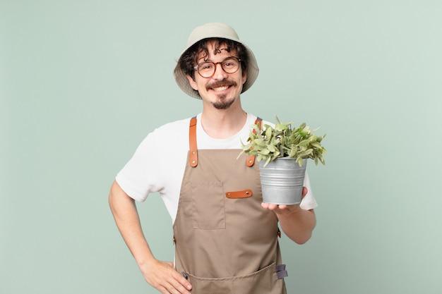 Jonge boer die gelukkig lacht met een hand op de heup en zelfverzekerd