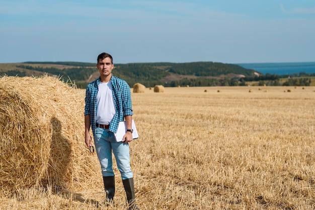Jonge boer in spijkerbroek, wit t-shirt, blauw shirt, rubberen laarzen in het veld met hooibergen met tablet en notebook, kopie ruimte, landbouwindustrie, landelijke bedrijfsconcept