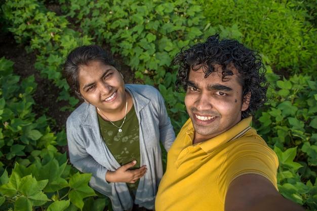 Jonge boer paar een selfie met een smartphone of camera in de katoenboerderij.