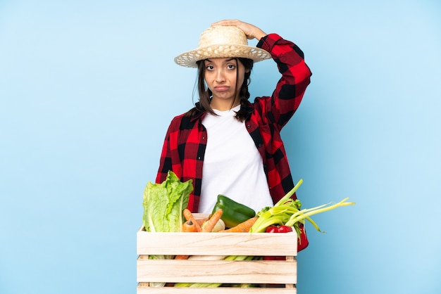 Jonge boer vrouw met verse groenten in een houten mandje met een uitdrukking van frustratie en niet begripvol