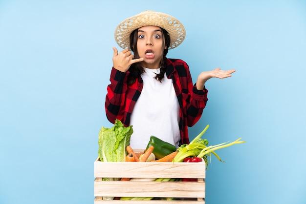 Jonge boer vrouw met verse groenten in een houten mandje