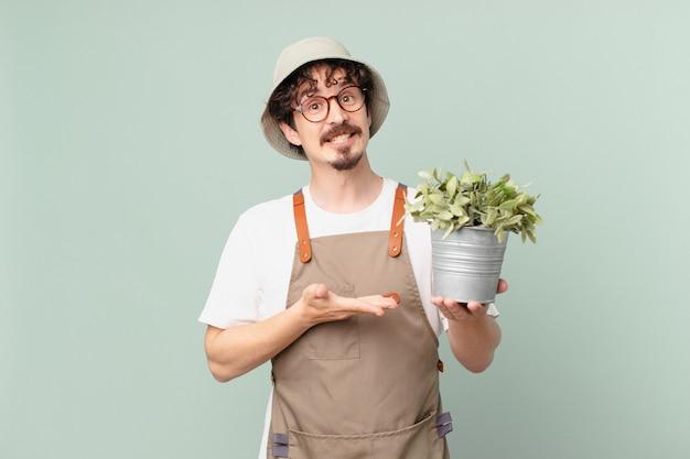 Jonge boerenman die vrolijk lacht, zich gelukkig voelt en een concept toont