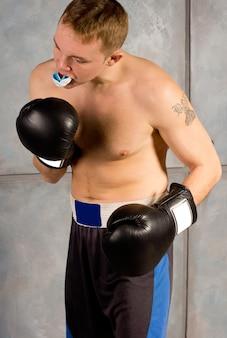 Jonge bokser die zijn gebitsbeschermer aanpast