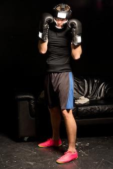 Jonge bokser op wacht met gehandschoende vuisten omhoog om zijn hoofd te beschermen tijdens een trainingstraining