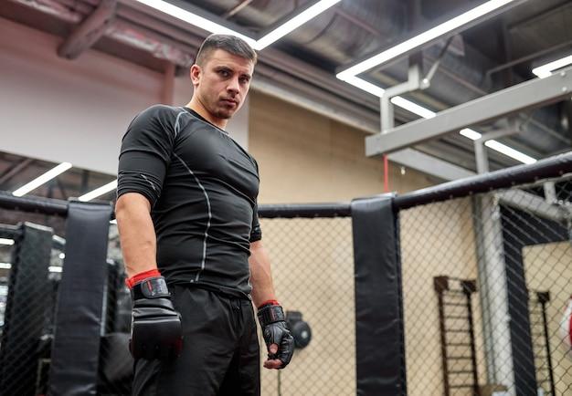 Jonge bokserman in zwarte kleding die zelfverzekerd naar de camera kijkt, voordat hij vecht, oefent kracht en kracht. mma, kickboksconcept
